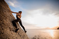 Female extreme climber conquers steep rock against the sunset over river. Royalty Free Stock Photo