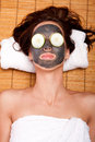 Female facial mask skincare spa woman face with beauty treatment and cucumber laying on bamboo at Stock Photo