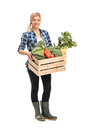 Female farmer holding a crate with vegetables full length portrait of agricultural worker full of fresh organic and looking at the Stock Images