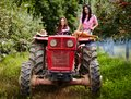 Female farmers driving the tractor two attractive in orchard Royalty Free Stock Images