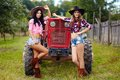 Female farmers with tractor two attractive leaning on the in the orchard Stock Image