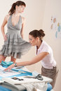Female fashion designer trying dress on model Stock Photos