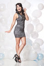 Female fashion model posing with a balloon background caucasian in grey cocktail dress in front of white and blue wall Royalty Free Stock Photos
