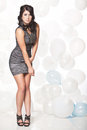 Female fashion model posing with a balloon background caucasian in grey cocktail dress in front of white and blue wall Royalty Free Stock Photo