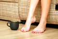 Female feet and a cup of tea or coffee Stock Images
