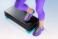 Female feet do exercise on fitness aerobic stepper in violet sneakers and violet sportswear a black turquoise and step top view Royalty Free Stock Photography
