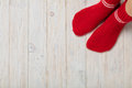 Female feet in knitted red socks on white wooden background. Royalty Free Stock Photo