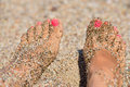 Female feet in the sand young woman s at beach with pink toe nails Royalty Free Stock Image