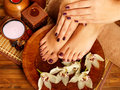 Female feet at spa salon on pedicure procedure closeup photo of a legs in water decoration the flowers Stock Images