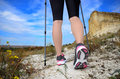 Female feet and trekking stick on the path Royalty Free Stock Images