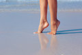 Female feet in water on the beach Royalty Free Stock Photo