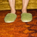 Female feet wearing slippers. Stock Photos