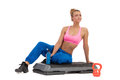 Female fitness instructor rest on aerobics step after kettle bell workout holding bottle with energy drink full length studio shot Royalty Free Stock Photos