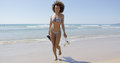 Female with flippers walking on beach Royalty Free Stock Photo