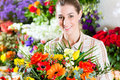 Female florist in flower shop or nursery presenting a bouquet of flowers Stock Photography