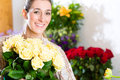 Female florist in flower shop or nursery presenting roses Royalty Free Stock Image