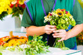 Female florist in flower shop or nursery presenting roses preparing a bouquet Royalty Free Stock Images
