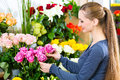 Female florist in flower shop or nursery presenting yellow roses Stock Photo