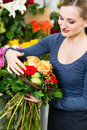 Female florist in flower shop or nursery presenting yellow roses Royalty Free Stock Photos