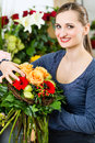 Female florist in flower shop or nursery presenting yellow roses Stock Photography