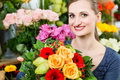 Female florist in flower shop or nursery presenting yellow roses Stock Images