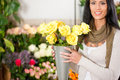 Female florist in flower shop or nursery presenting yellow roses Royalty Free Stock Image
