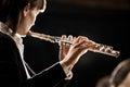 Female flutist performing elegant playing flute on dark background Royalty Free Stock Image