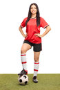 Female football player stepping over a ball full length portrait of young on grass field and looking at the camera isolated on Royalty Free Stock Photo