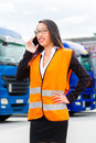 Female forwarder in front of trucks on a depot logistics asian or supervisor with mobile phone and trailers transshipment point Stock Photography