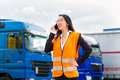 Female forwarder in front of trucks on a depot logistics asian or supervisor with mobile phone and trailers transshipment point Royalty Free Stock Images
