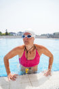 Female freediver at pool wearing goggles lifting herself up edge of outdoor swimming Royalty Free Stock Photo