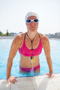 Female freediver at pool wearing goggles lifting herself up edge of outdoor swimming Stock Photography