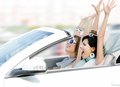 Female friends in the cabriolet with hands up Royalty Free Stock Photos