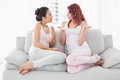 Female friends chatting in the living room relaxed young at home Stock Photos