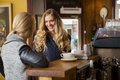 Female friends conversing by counter happy in coffeeshop Royalty Free Stock Image