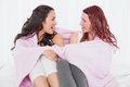 Female friends covered in sheet while chatting on bed relaxed young at home Stock Image