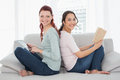 Female friends with digital tablet and book at home side view portrait of two relaxed young on sofa Royalty Free Stock Images