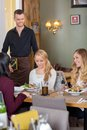 Female friends with food on table while waiter young holding menu at cafe Stock Photos