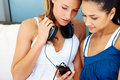 Female friends listening to music on mobile phone Stock Images