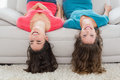 Female friends lying upside down on sofa at home portrait of two smiling young in living room Royalty Free Stock Images