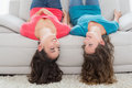 Female friends lying upside down on sofa at home two smiling young in living room Royalty Free Stock Photo