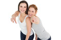 Female friends pointing against white background portrait of two young Stock Photos