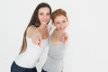 Female friends pointing against white background portrait of two young Stock Photo