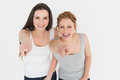 Female friends pointing against white background portrait of two young Stock Images