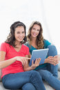 Female friends using digital tablet in the living room portrait of two smiling young at home Stock Photo