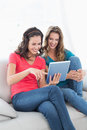Female friends using digital tablet in the living room two smiling young at home Stock Photography