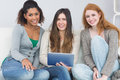 Female friends using digital tablet together on sofa portrait of young at home Royalty Free Stock Image