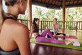 Female friends during yoga class break at fitness center shot of young relaxing on mat and talking after workout session Royalty Free Stock Photography
