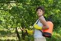 Female gardener with knapsack garden spray Royalty Free Stock Photo