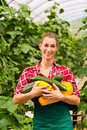 Female gardener at market gardening or nursery with apron and vegetables Stock Photos